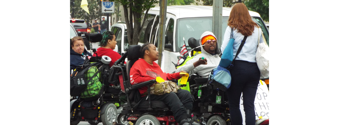 Picture of ADAPT activists handing out flyers on JRC / #StopTheShock